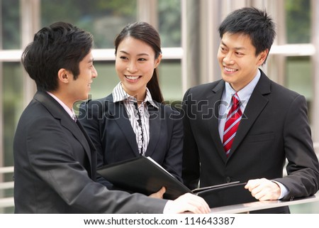 Three Business Colleagues Discussing Document Outside Office