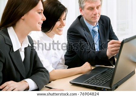 Three business colleagues sitting around table and working together, looking at monitor