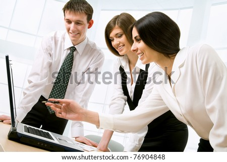 Three business colleagues standing around table and working together, looking at monitor, smiling