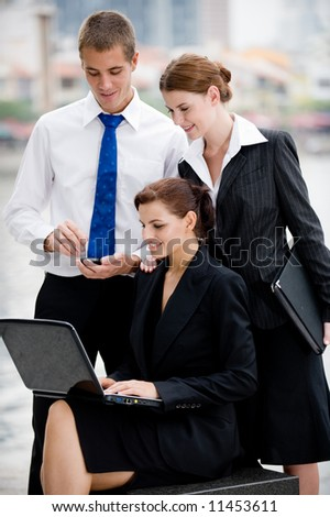 Three business executives with laptop outside by a river in the City