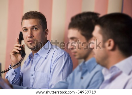 Three business men operators working in office,focus on last man having a conversation by telephone