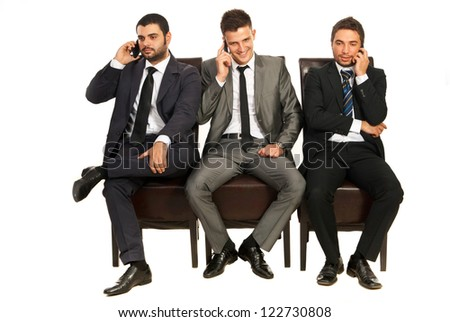 Three business men sitting on chairs in a line and speaking by phones mobile isolated on white background