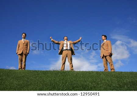 Three business men with different posture at the top of a hill