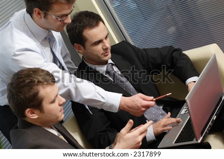 Three business men working together on laptop in the office. one is standing two are sitting on leather sofa - close up