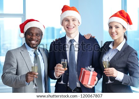Three business partners in Santa caps holding champagne and wishing you merry Christmas
