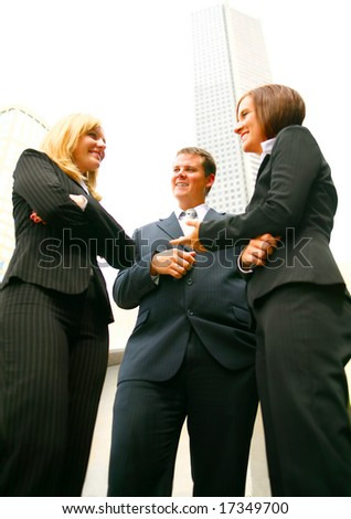 three business people discuss as a team outdoor with tall downtown building on the background