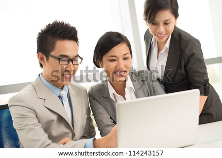 Three business people discussing documents on computer
