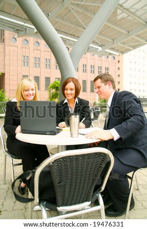 three business people having a group meeting outdoor in modern cafe setting area
