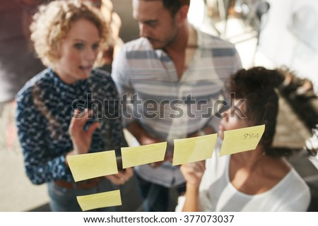 Three business people having a meeting in office. They are standing in front of glass wall with post it notes and discussing.