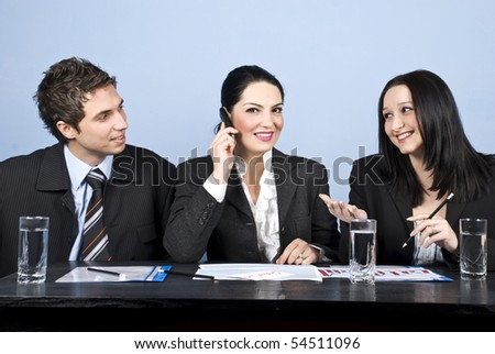 Three business people having a meeting,the middle businesswoman speaking at phone mobile and the other two people having an conversation and laughing together