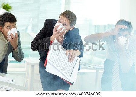 Three business people in gas masks gasping in office