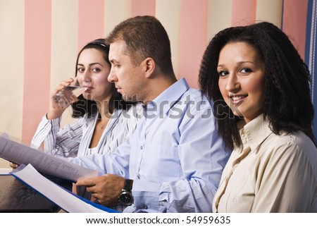 Three business people in office at work,man in middle reading some papers,last businesswoman drinking water,focus on first woman smile