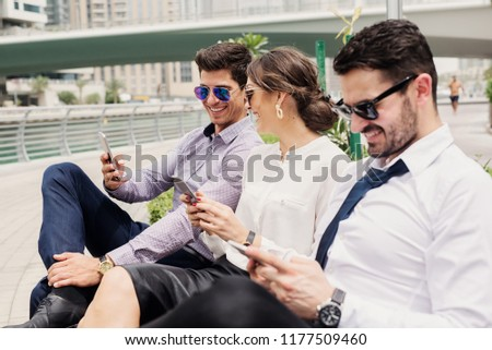 Three business people in suit taking a break from hard work . Sitting outside in Dubai Marina and having fun surfing on internet.