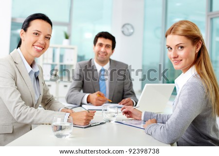 Three business people looking at camera in office