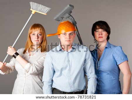three business people on gray background with cleaning instruments - stock photo