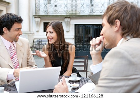 Three business people sharing a table at a coffee shop terrace, having a conversation during a meeting and using technology in the financial city district.