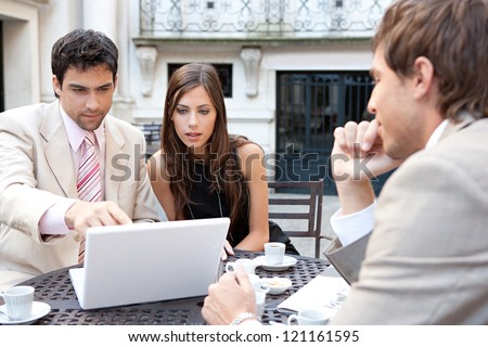 Three business people sharing a table at a coffee shop terrace, having a meeting and talking while using technology in the financial city district.