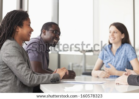 Three business people sitting at conference table and discussing during business meeting