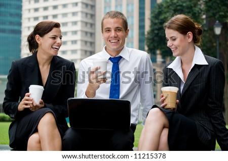 Three business people sitting outside having coffee break