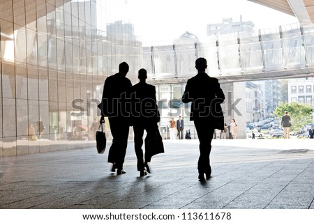 Three business people walking down the street talking. Silhouettes. Motion Blur.
