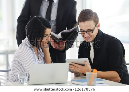 Three business people working at office with paperwork using tablet and laptop - stock photo