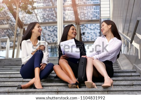 Three business women of different ethnicities talk about finance looking at the patterns of economic markets and banks, and in the background a group of multi-ethnic business people. #1104831992