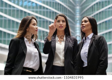 Three business women of different ethnicities talk about finance looking at the patterns of economic markets and banks, and in the background a group of multi-ethnic business people. #1104831995