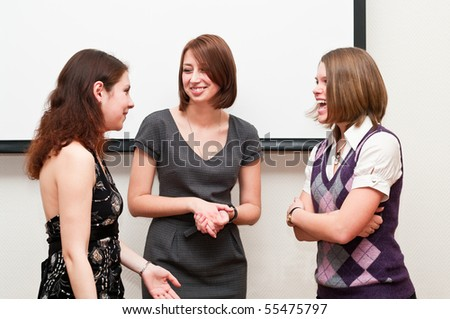 Three business women talking together in office room