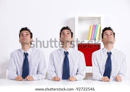 Three businessman at the office desk looking up