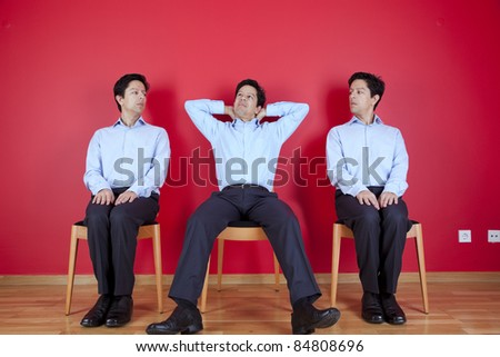 three businessman one happy and two with a suspicion look, next to a red wall