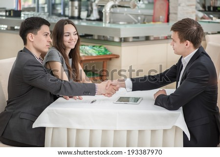 Three businessmen shaking hands at the table. Top view of a young and confident young people. Business people sitting in the restaurant at the meeting.