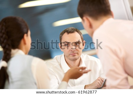 Three businessmen sitting at table and communicating, two of them defocused