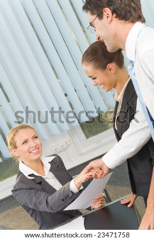 Three businesspeople cheering by handshake at office