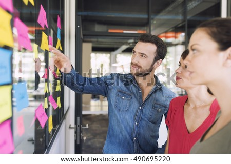 Three businesspeople discussing and planning concept. Front of glass wall marker and stickers. Startup office.