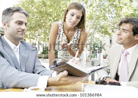Three businesspeople having a meeting while in a coffee shop'ts terrace in the city.