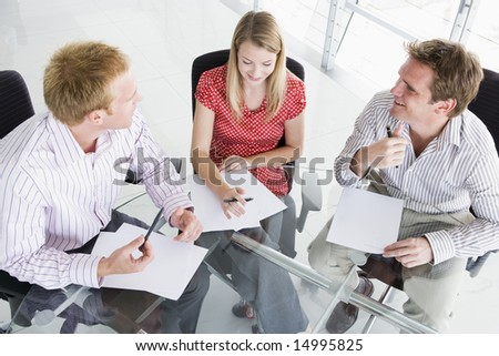 Three businesspeople in a boardroom looking at paperwork