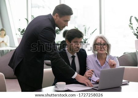 Three businesspeople partners looks at pc screen analyzing financial data company state prepare report, brainstorming about new forecast project details, teamwork business negotiations meeting concept