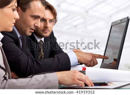 three businesspeople sitting by a laptop male is pointing at it