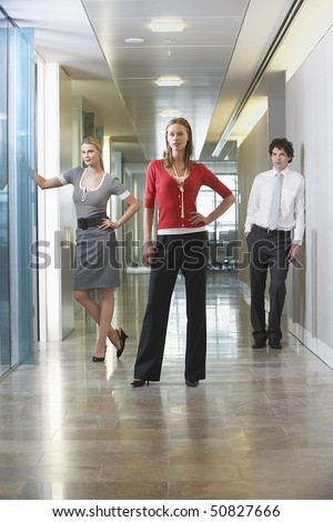 Three businesspeople standing in office corridor, portrait