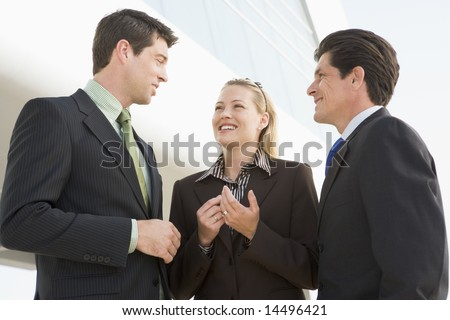 Three businesspeople standing outdoors by building talking and smiling