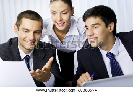 Three businesspeople working with laptop at office