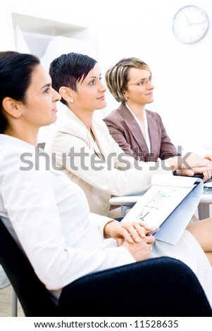 Three businesswoman attending on business training. Sitting in a row, making notes, smiling.