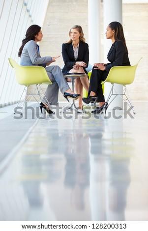 Three Businesswomen Meeting Around Table In Modern Office