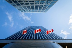 Three Canadian flags in front of a business building in Ottawa, Ontario, Canada. Ottawa is the capital city of Canada, and one of the main economic, political and business hubs of North America