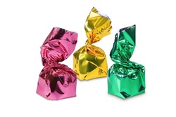 Three candies in pink, yellow and green wrapper isolated on white background