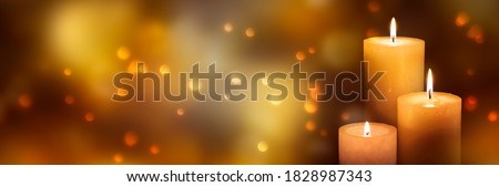 Photo of  three candle lights at the edge of blurred festive background, decorative golden shiny candle lights