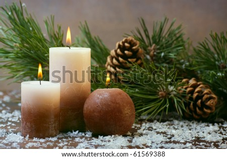 Three candles and pine branches with cones
