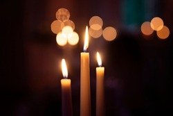 Three candles burning with flame and beautiful  bokeh in the background