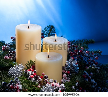 Three candles in an advent flower arrangement for advent and Christmas