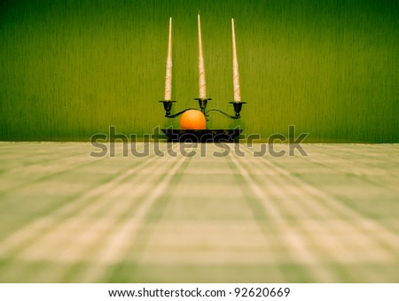 Three candles, silver plate and ripe orange on the green textured wall background